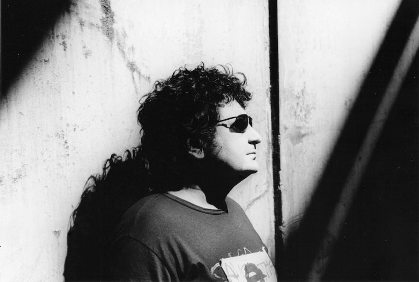 Richard Clapton leaning against wall with sunglasses on